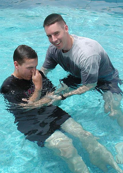 A photo of an adult male being baptised by immersion.