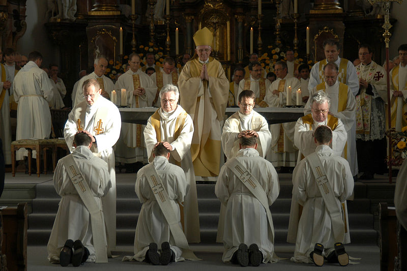 Are Seminaries Biblical?: A photo of four priests laying their hands on four kneeling men receiving the rite of ordination.