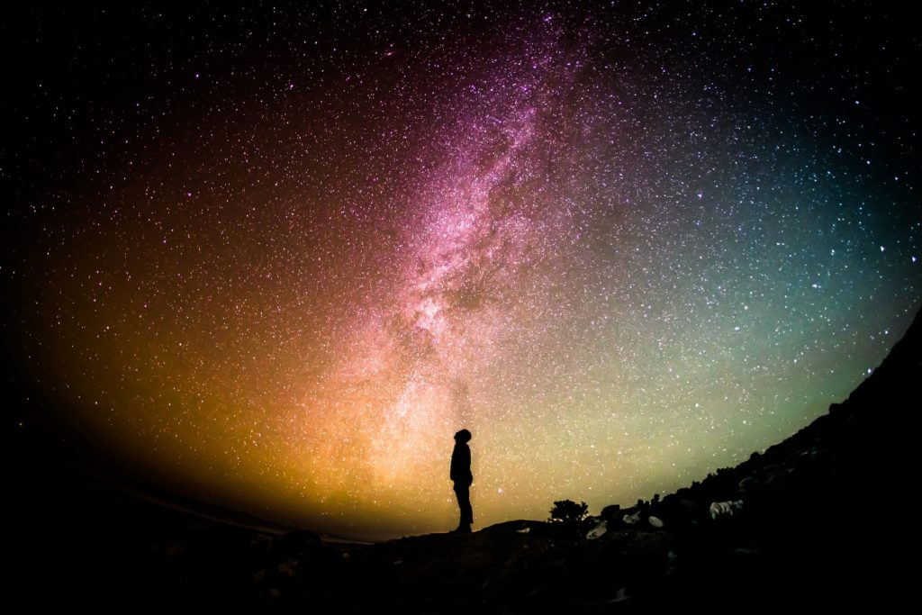 A wide-angle view of the Milky Way with a silhouette of a man looking skyward. Does election depend on our works?