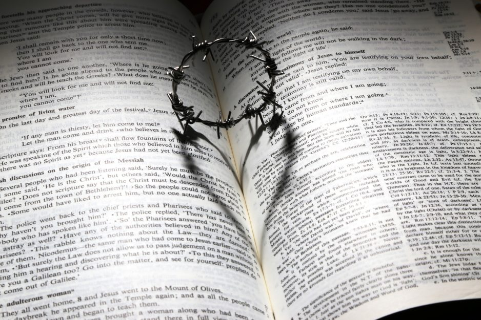 An open Bible with a miniature crown of thorns resting on the binding and gutter between the left and right pages. How is the Bible the Word of God?